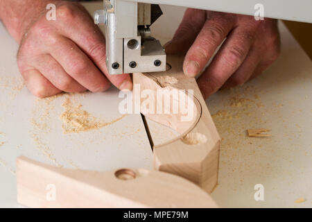 Carpenter tools on wooden table with sawdust. Band-saw to cut an intricate shape in a piece of wood.Carpenter workplace. - Stock Photo