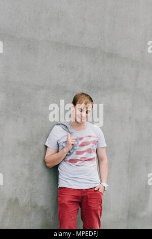 Portrait of a stylish man on a background of concrete structures. - Stock Photo