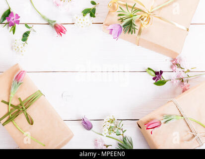 Gift and roses on wooden white background. Workspace. Top view, flat lay - Stock Photo