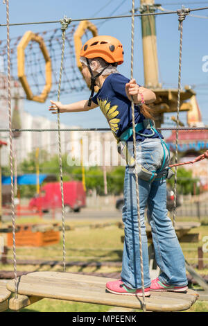 cute baby girl in climbing gear on a rope park background. Little beautiful girl climbs on rope harness in summer city park. - Stock Photo