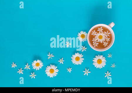 Cup of tea with fresh flowers blossom bouquets on blue surface. Flat lay, top view food floral background. - Stock Photo