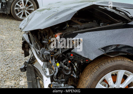 Broken car after accident, view of car front down after an explosion, ready to be scrapped - Stock Photo