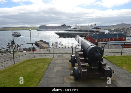 Cruise ships visiting Lerwick harbour with tenders ferrying them to the shore, taken from Fort Charlotte Lerwick with cannons in the placements - Stock Photo