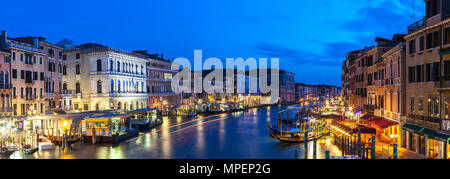 Stitched panorama of the Grand Canal at blue hour from the Rialto bridge, Venice,  Veneto, Italy with historic palazzos, gondolas, tourists at the vap - Stock Photo
