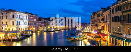 Stitched panorama view at blue hour from the Rialto Bridge of the Grand Canal, Venice, Veneto, Italy with light reflections, illuminated  historic pal - Stock Photo