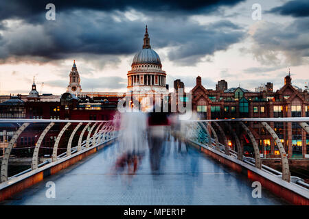 Early evening on London's Millennium Bridge with people crossing in motion blur and a view of St Pauls Cathedral. - Stock Photo