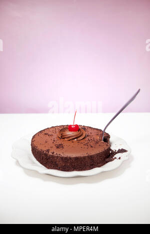 Chocolate cake with cherry on top and fork sticking in it - Stock Photo