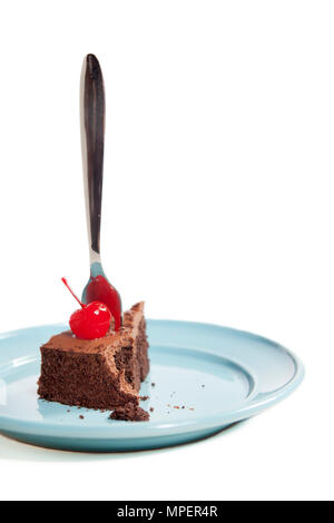 Chocolate cake with cherry on top and fork sticking in it on a blue plate - Stock Photo