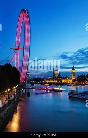 LONDON - September 13, 2015: View of London Eye at night with Thames river in London, England. London Eye is a famous tourist attraction at a height o - Stock Photo