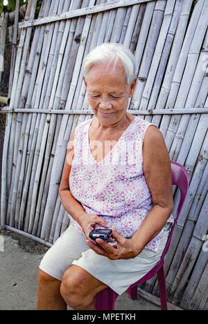Senior, elderly white-haired Filipino Asian woman sitting outdoors trying to use her smartphone. Philippines. - Stock Photo