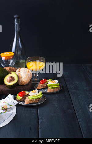 Tasty and juice , sandwich with avocado, tomato and poached egg on wooden chopping board, close up, selective focus. Healthy delicious breakfast - Stock Photo