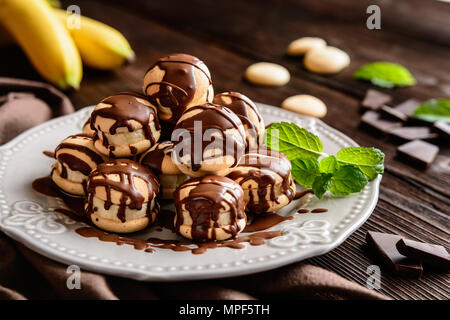 Round sponge biscuits stuffed with banana slices and topped with chocolate - Stock Photo