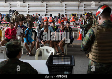 Military and civilian role players from the Thailand, Malaysia,  Japan and the U.S. sit in a holding area during a noncombatant  evacuation operation exercise during Cobra Gold  2017 at Utapao International Airport in Rayong Province,  Thailand, Feb. 19, 2017. Cobra Gold, in its 36th iteration,  focuses on humanitarian civic action, community  engagement, and medical activities to support the needs  and humanitarian interest of civilian populations around the  region. (U.S. Marine Corps photo by Lance Cpl. Daniel R.  Betancourt Jr.) - Stock Photo