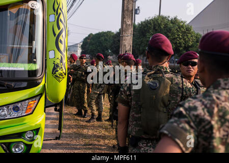 Malaysian Army soldiers with 10th Paratrooper Brigade  unload a bus during a non-combatant evacuation operation exercise during Cobra Gold 2017 at Utapao International Airport in Rayong Province, Thailand, Feb. 19, 2017. Cobra Gold, in its 36th iteration, focuses on humanitarian civic action, community engagement, and medical activities to support the needs and humanitarian interest of civilian populations around the region. (U.S. Marine Corps photo by Lance Cpl. Daniel R. Betancourt Jr.) - Stock Photo