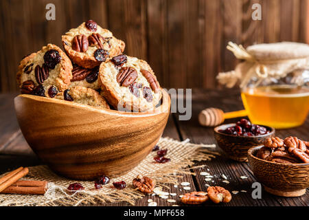 Homemade whole wheat oatmeal cookies with pecan nuts, dried cranberries and honey - Stock Photo