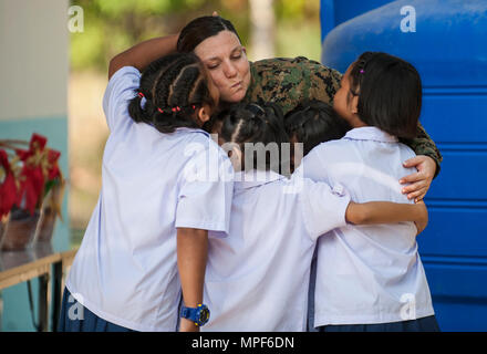 RAYONG PROVINCE, Thailand (Feb. 21, 2017) – Hospital Corpsman 1st Class Samantha Clark, assigned to 1 Marine Expeditionary Force Headquarters Group, bids farewell to Thai students during a dedication ceremony, marking the completion of the Ban Nong Muang school expansion project. The project was a joint effort by the U.S. Naval Mobile Construction Battalion 5, Construction and Developmental Regiment, Sattahip Naval Base and Korean Naval Mobile Construction Battalion 2nd Engineer, part of Cobra Gold 2017. Cobra Gold, in its 36th iteration, is the largest Theater Security Cooperation exercise in - Stock Photo