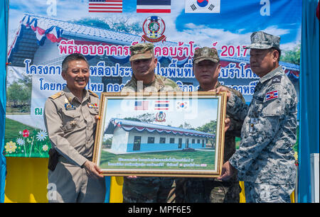 RAYONG PROVINCE, Thailand (Feb. 21, 2017) – (From left to right) Gov. Surasak Charoensirichot, Rayong provincial governor, Brig. Gen. Bryan Suntheimer, United States Army Pacific Deputy Commanding General for Army National Guard, Rear Adm. Jong Sam Kim, commander, Republic of Korea Navy Component 5 and Vice Adm. Panya Lekbua, deputy commander-in-chief, Royal Thai Fleet stand on stage to receive a plaque during a dedication ceremony, marking the completion of the Ban Nong Muang school expansion project. The project was a joint effort by the U.S. Naval Mobile Construction Battalion 5, Constructi - Stock Photo