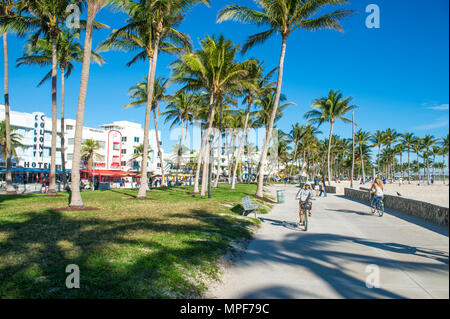 MIAMI - DECEMBER 27, 2017: Cyclists and joggers share the morning beachfront boardwalk promenade at Lummus Park in South Beach. - Stock Photo