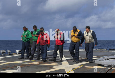 170220-N-RM689-008  SOUTH CHINA SEA (Feb. 20, 2017) Sailors perform a foreign object debrief walk down to prepare for an MH-60R Sea Hawk helicopter, attached to Helicopter Maritime Strike Squadron (HSM) 78, to land on the flight deck of Arleigh Burke-class guided-missile destroyer USS Wayne E. Meyer (DDG 108) to prepare for a replenishment-at-sea with Henry J. Kaiser-class underway replenishment oiler USNS Tippecanoe (T-AO 199). Wayne E. Meyer is on a regularly scheduled Western Pacific deployment with the Carl Vinson Carrier Strike Group as part of the U.S. Pacific Fleet-led initiative to ext - Stock Photo