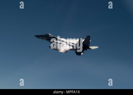 A U.S. Air Force 44th Fighter Squadron F-15 Eagle flies over the Pacific Ocean during a training exercise Feb. 16, 2017. The 44th FS Vampire Bats bear the responsibility of working together with joint U.S. and Japanese forces to enhance peace and security for assets and allies in Japan and throughout the Indo-Asia Pacific Theater. (U.S. Air Force photo by Staff Sgt. Peter Reft/Released) - Stock Photo