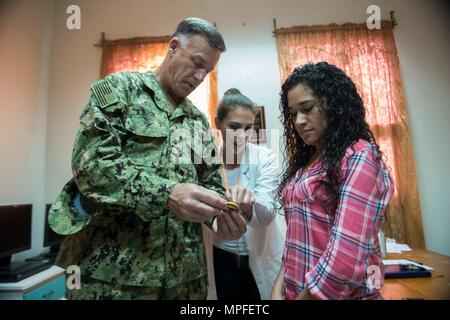 170223-N-YM856-041 TRUJILLO, Honduras (Feb. 23, 2017) - Commander, U.S. Naval Forces Southern Command/U.S. 4th Fleet (USNAVSO/FOURTHFLT) Rear Adm. Sean S. Buck presents his command coin to Hospital Salvador Paredes Sub-Director Dr. Xiomara Arita during a tour of the facility in support of Continuing Promise 2017's (CP-17) visit to Trujillo, Honduras. CP-17 is a U.S. Southern Command-sponsored and U.S. Naval Forces Southern Command/U.S. 4th Fleet-conducted deployment to conduct civil-military operations including humanitarian assistance, training engagements, and medical, dental, and veterinary - Stock Photo
