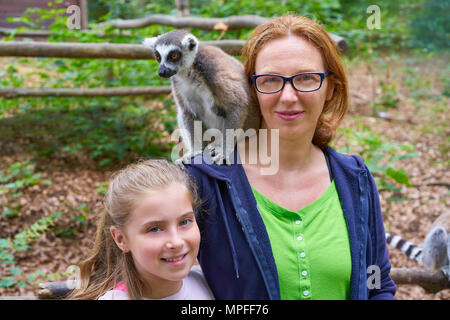 mother and daughter having fun with ring tailed lemur animal outdoor - Stock Photo