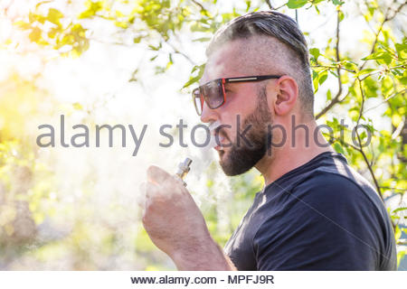 Portrait of young guy with beard in cap and sunglasses vaping an electronic cigarette with puffs of steam at sunset - Stock Photo