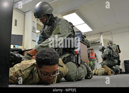 FORT SHAFTER, Hawaii- Members of the Special Reaction Team (SRT), 39th Military Police Detachment, 728th MP Battalion, 8th MP Brigade, 8th Theater Sustainment Command, secure two Soldiers with hand restraints during an active shooter training exercise Feb. 23, here. (U.S. Army photo by Staff Sgt. Taresha Hill) - Stock Photo