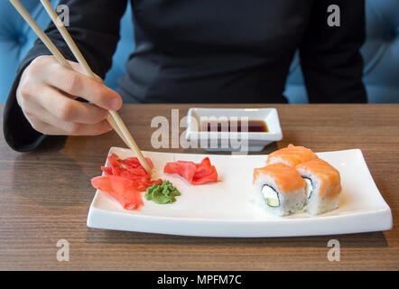 Sushi rolls on plate in cafe takes woman's hand with chopsticks - Stock Photo