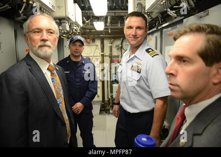 Coast Guard Lt. Cmdr. Joe Rizzo, cutter Lawrence Lawson commanding officer, and Chief Petty Officer David Quigley, ship's engineering petty officer, provide a tour of the cutter's engine room to Reps. Dan Newhouse and Chuck Fleischmann, while in Washington, D.C., Thursday, Mar. 9, 2017. The U.S. Representatives had an opportunity to tour the newest ship in the Coast Guard fleet prior to its Mar. 18, 2017 commissioning in Cape May, N.J. U.S. Coast Guard photo by Petty Officer 2nd Class Barry Bena - Stock Photo