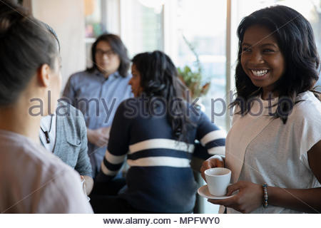 Smiling, happy young woman drinking coffee and talking in cafe - Stock Photo