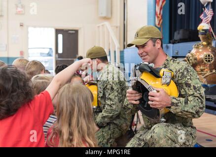 U.S. Navy Diver 1st Class Jason Thurston, assigned to Mobile Diving and Salvage Unit (MDSU) 2, talks about the KM-37 diving helmet to kindergarten students during a community outreach event at Central Elementary School in Maple, N.C., March 8, 2017. (U.S. Navy photo by Mass Communication Specialist 2nd Class Charles Oki) - Stock Photo