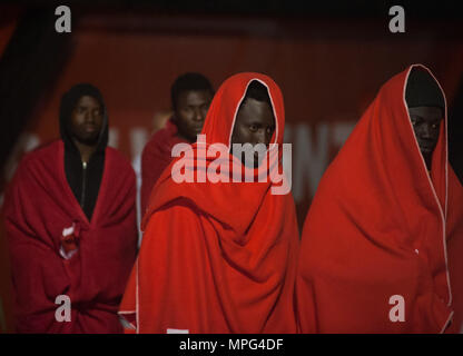 Malaga, Spain. 22nd May, 2018. Migrants are seen covered by red blanket after their arrival. Arrival of a group of migrants rescued in the Mediterranean Sea from a dinghy near the Malaga coast. Aboard of a two boats, members of the Spanish Maritime Safety rescued 94 migrants this early morning and brought to Malaga port. Credit: Jesus Merida/SOPA Images/ZUMA Wire/Alamy Live News - Stock Photo