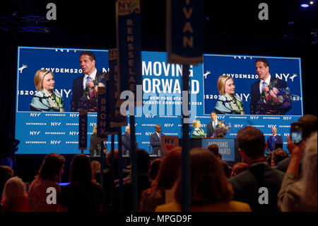 Hempstead, New York, USA. 23rd May, 2018. HILLARY CLINTON and Governor ANDREW CUOMO, with a bouquet of flowers for Clinton, speak on stage during Day 1 of New York State Democratic Convention, held at Hofstra University on Long Island. Clinton, the former First Lady and NYS Senator, endorsed the re-election of Gov. A. Cuomo for a third term. Credit: Ann Parry/ZUMA Wire/Alamy Live News - Stock Photo