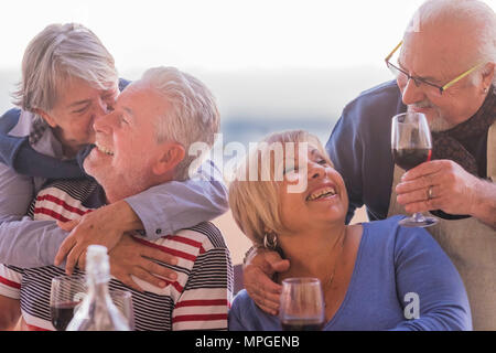 causasian mature couples friends having fun during evening dinner together. kiss and hug and smile and laugh for great retired lifestyle concept. outd - Stock Photo