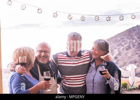 group of 4 seniors, two couples, stay togheter and have fun enjoing a cup of wine outdoor in the rooftop. vacation elderly concept and friendship. sun - Stock Photo