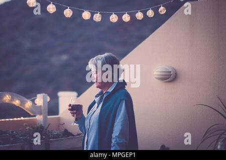 aged senior woman drink some wine during a celebration event by night in vacation. summer style and mountains nature view. beautiful adult model lifes - Stock Photo