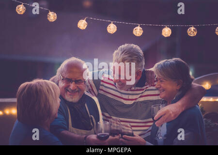 Focus on the man. group of senior adult aged doing party night on the rooftop at home. everybody hug together and smile and laugh for a nice activity  - Stock Photo