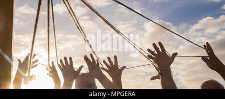 teamwork of elderly people group with a lot of hands united between a cord under the sunlight. all hands together with beautiful sky on the background - Stock Photo