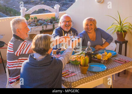 adult group of people having nice dinner outdoor in the terrace. enjoy the friendship with time together drinking and celebrating holiday or retired c - Stock Photo