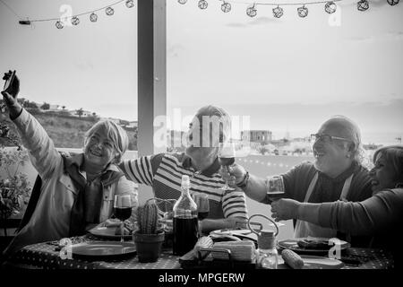 group of aged senior friends adults having dinner and doing party nice time in the rooftop terrace outdoor with wine and food. having fun during the s - Stock Photo