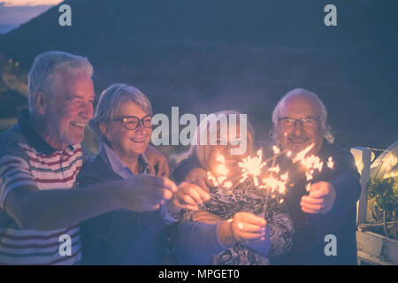 celebrate event new year eve at midnight for group of nice people beautiful senior adult. men and women with sparkles outdoor by night - Stock Photo