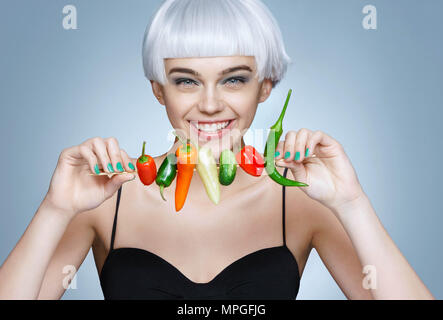 Beautiful young girl with different peppers. Photo of smiling blonde girl with flawless skin on blue background. Healthy lifestyle - Stock Photo