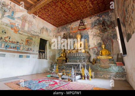 Murals, altar and Buddha statues inside of Wat Pa Huak temple in Luang Prabang, Laos. - Stock Photo