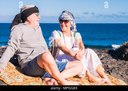 happy couple of senior people gentleman and lady sit down near the ocean with hippy colored clothes style. enjoy and have fun with alternative lifesty - Stock Photo