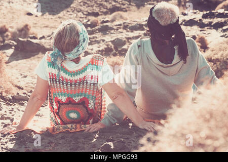 man and woman senior aged grandfathers stay on the rocks feeling the nature, hippy style and vintage filter with colored clothes in sunny day - Stock Photo