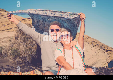 retired and vacation freedom concept for hippy senior couple man and woman playing with the wind with colored clotehs. pastel tones and blue sky for s - Stock Photo