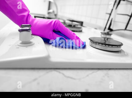Hand in rubber gloves cleans a kitchen gas stove. - Stock Photo