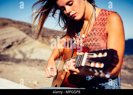 nice caucasian blonde girl playing guitar outdoor in tenerife. frredom and hippy vacation concept. beautiful face doing music. - Stock Photo