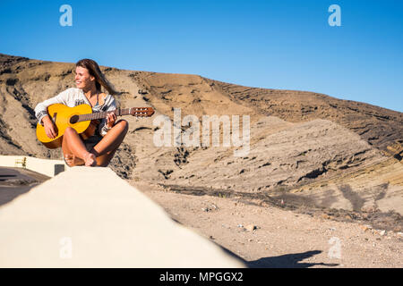 nippy and alternative lifestyle concept for blonde caucasian model smiling outdoor with mountains on the background and playing an old acoustic guitar - Stock Photo